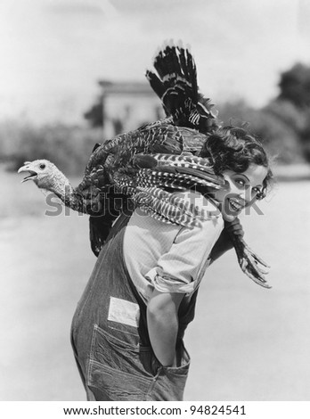 Portrait of woman with live turkey slung over shoulder