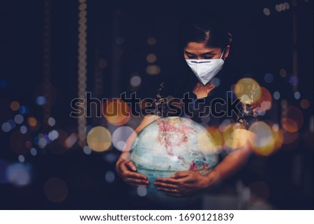 Portrait of Woman with mask N 95  is holding world globe while praying to God over black background with bokeh light in the night. Virus Covid 19 crisis, Disease  concept with copy space Foto stock ©