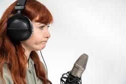 Portrait of woman with red hair infront of white background sitting idealess infront of a microphone