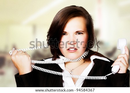 portrait of woman with telephone cord wrapped around face - stock photo