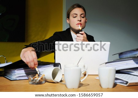 Portrait of woman working and smoking cigarette