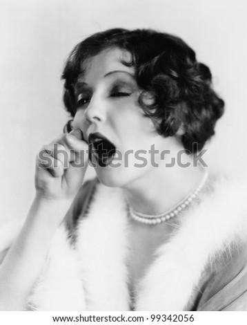 Portrait of woman yawning