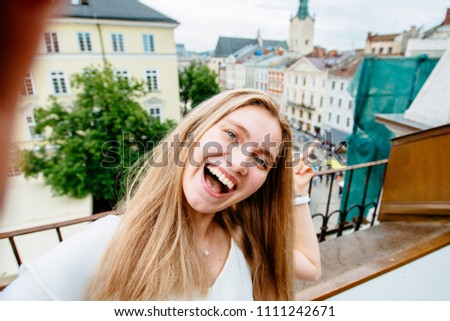 Portrait of wonderful white blond woman model expressing energy in good day in Europe. Lovely female making selfie while relaxing on terrace with city view past old building.