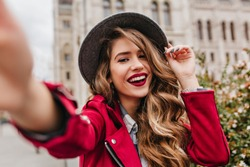 Portrait of wonderful white female model with bright makeup expressing energy in good day in Europe. Lovely curly woman in stylish hat making selfie while walking past old building.