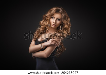 Stock Photo Portrait of wonderful young blonde woman with long hair looking at camera. Sexy girl in blue dress. Jewelry. Hairstyle. Glamour makeup. Vogue. Curly hair.