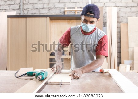 portrait of worker at carpenter workspace cutting the wood board using saw table