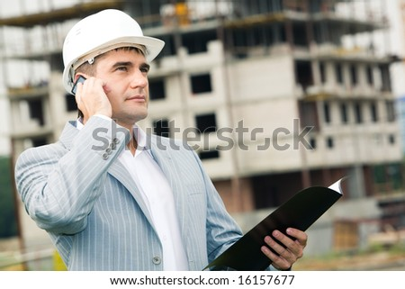 Portrait of worker speaking on the phone at building site - stock photo