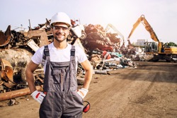 Portrait of worker standing in metal junk yard with crane lifting scrap metal for recycling.