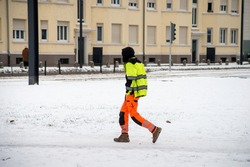 Portrait of worker walking in the street covered by the snow