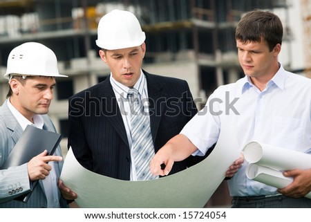 Portrait of workgroup of builders looking at new project in bossâ?? hands while one of men pointing at something