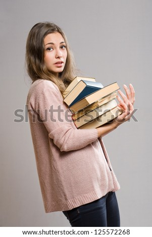 Portrait of worried looking young brunette with large pile of books.