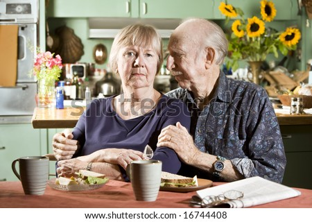 Portrait of Worried Senior Couple in their Dining Room