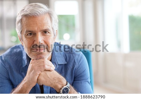 Portrait of 60-year-old man with grey hair and blue shirt looking at camera Zdjęcia stock ©