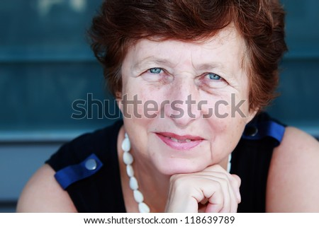 Portrait of 65-years-old beautiful woman outdoors