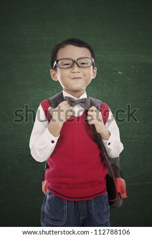 Portrait of 5 years old boy standing in front of blackboard and ready to school