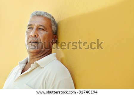 portrait of 50 years old latin american man having problems and leaning on yellow wall. Horizontal shape, copy space