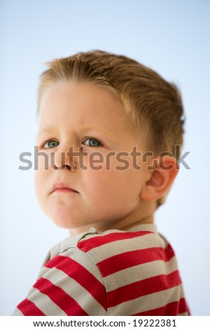 Portrait of 4 years old unhappy boy outdoors