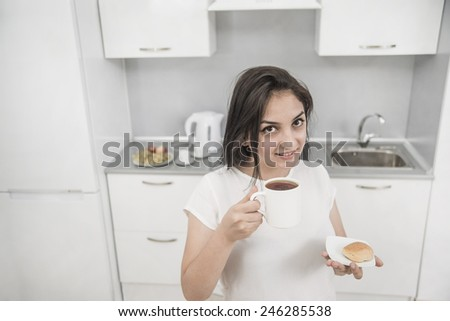 Portrait of Young adult brunette asian woman drink black or green tea on kitchen room interior background Young adult girl hold in hand cookie on dish plate Empty copy space for inscription