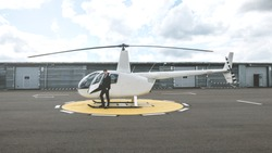 Portrait of young adult businessman executive standing near a private charter helicopter on a helipad