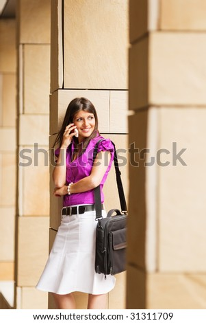 portrait of young adult businesswoman talking on the phone and leaning on column. - stock photo