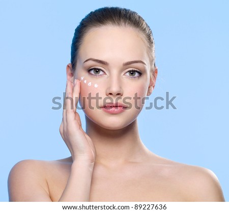 stock photo : Portrait of young adult girl applying cream on her skin around ...