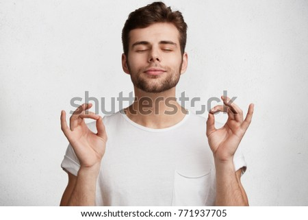 Portrait of young adult male with beard, stands in yoga pose, tries to concentrate and feel relaxation after work, isolated over white background. People, meditation and mental practice concept #771937705