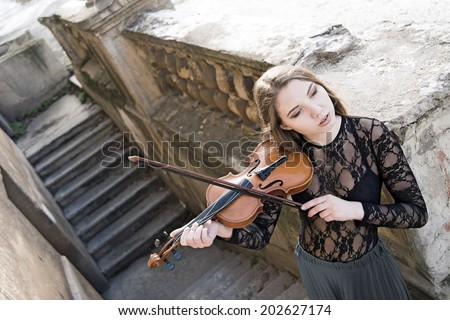Portrait of Young adult sexy girl with long brown hair with a broken violin on old retro fence and concrete stairway in the Gothic style of classicism Cute slim woman wearint transparent black shirt
