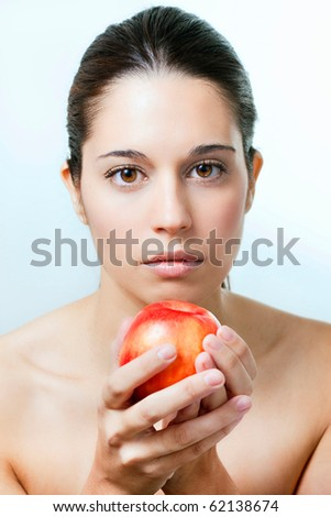 Portrait of young adult woman with red apple - stock photo