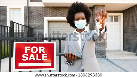 Portrait of young African American beautiful woman real-estate agent standing outdoors at house with board For sale. Female in medical mask showing and handing keys from dwelling at outskirt to camera
