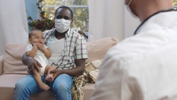 Portrait of young african-american dad in mask holding cute baby and listening to doctor during medical checkup at home. Pediatrics visiting single father with newborn son