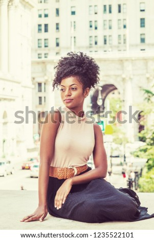 Portrait of Young African American Female College Student, with afro hairstyle, wearing sleeveless top, skirt, bending legs, sitting on street by vintage style office building in New York, thinking.