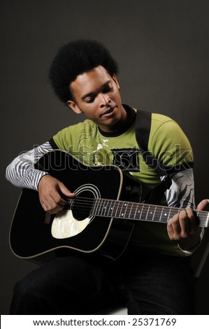 Portrait of young african american man playing acoustic guitar