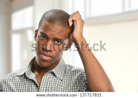 Portrait of young African American man scratching head indoors