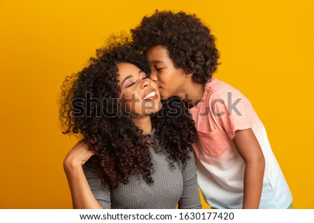 Portrait of young African American mother with toddler son. Son kissing his mother. Yellow background. Brazilian family.
