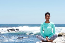 Portrait of young african american woman doing yoga at the beach
