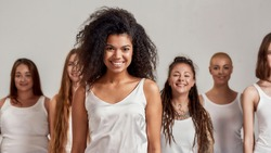 Portrait of young african american woman in white shirt smiling at camera. Group of diverse women standing isolated over grey background. Selective focus. Front view. Web Banner