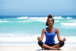 Portrait of young african american woman meditating in yoga pose outdoors at the beach
