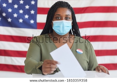Portrait of young African-American woman wearing mask putting vote bulletin in ballot box and looking at camera while standing against American flag on election day, copy space