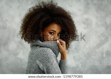 Portrait of young african american woman with an afro hair wear high-neck wool and cashmere sweater, hiding her mouth under the golf
