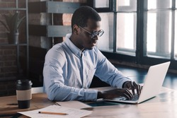 Portrait of young african business man sitting at his desk in loft office, typing message using laptop