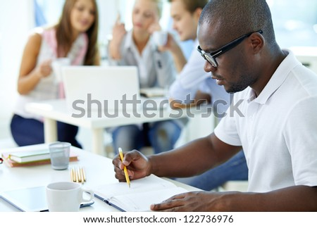 Portrait of young African guy looking in notepad in working environment