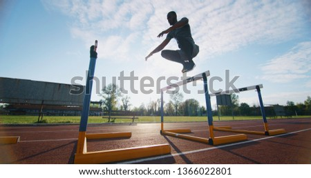 Portrait of young african male athlete is jumping on race track in athletics stadium. #1366022801