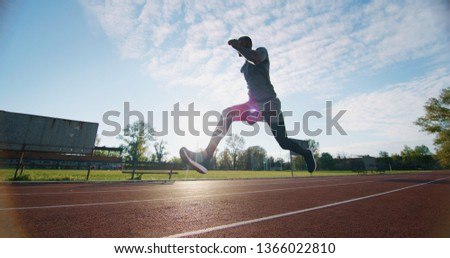 Portrait of young african male athlete is jumping on race track in athletics stadium. #1366022810
