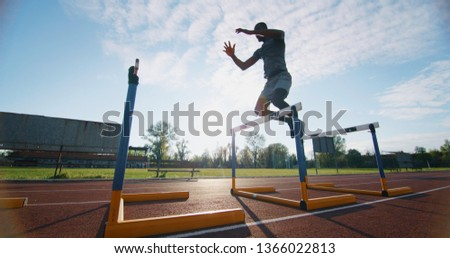 Portrait of young african male athlete is jumping on race track in athletics stadium. #1366022813