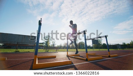 Portrait of young african male athlete is jumping on race track in athletics stadium.