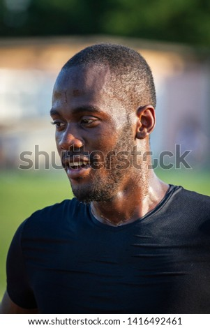 Portrait of young african male athlete sweat after a race in athletics stadium with sunshine.