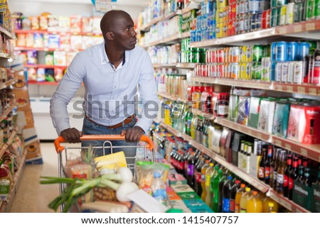Portrait of young African male with grocery cart buying food products in supermarket