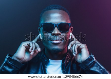 Portrait of young african man listening music with wireless earphones #1295486674