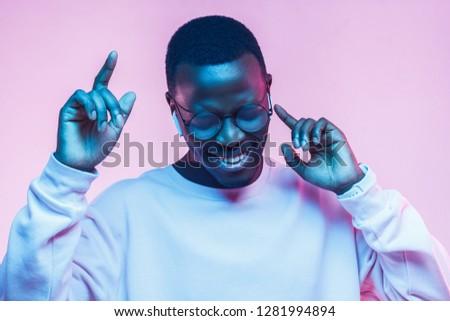 Portrait of young african man listening music with wireless earphones, dancing, wearing gray sweatshirt