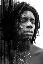 Portrait of young african man with closed eyes and traditional face paint shot at a three quarters angle